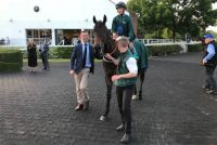 A delighted trainer walks his winner into the winners enclosure