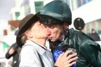 Flat jockey George Baker recieves a peck from a thrilled winning owner!