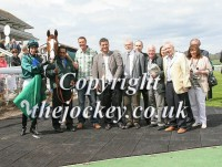Jupiter Storm poses with his owners and jockey George Baker