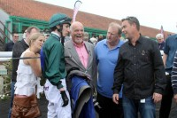 Jockey George Baker gives owners a debrief after the race