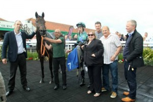 Lightning Spirit in the winners enclosure with her adoring owners