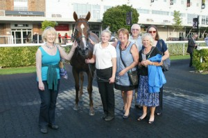 A smiley crowd of owners with their winning filly