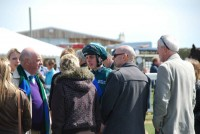 Jockey Ned Curtis giving a debrief to owners after his first ride