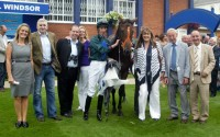 The owners gather around their winner with jockey George Baker