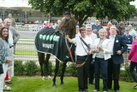 Owners gather with their winner and his delighted stable lad